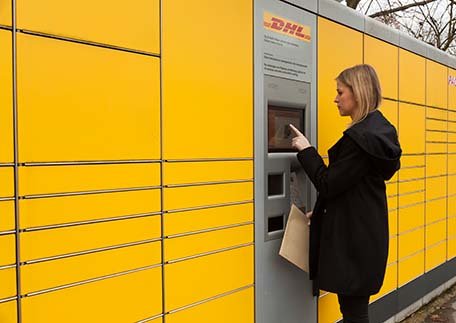 Kollegin an der DHL- Packstation | AXA